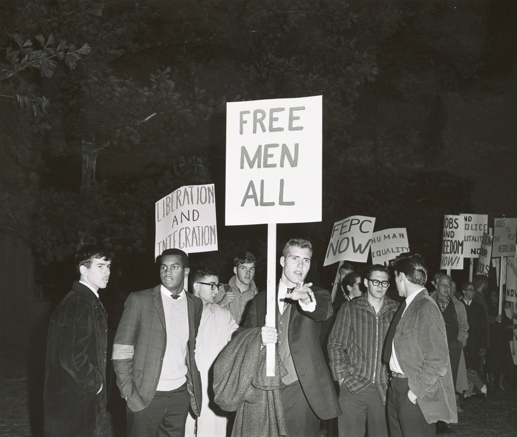 "This photograph, captured outside of Leverone Field House during Alabama Governor George Wallace's visit to Dartmouth on November 5, 1963, depicts Dartmouth students (including Richard Joseph '65) and Upper Valley community members protesting the segregationist's policies and views on race. Signs reading ""liberation and integration"" and ""free men all"" are raised in response to the politician's recent inaugural address, in which Wallace stated, ""segregation now, segregation tomorrow, segregation forever."" Additional signs reference FEPC, or the Fair Employment Practices Committee, which was established by President Franklin D. Roosevelt in 1941 to help prevent discrimination against African-Americans in defense and government jobs."