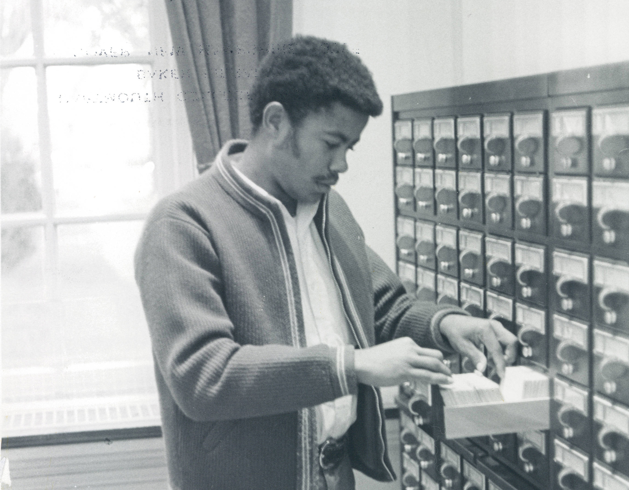 "A photo of a Black student using the Baker-Berry card catalog featured in ""The Black Student at Dartmouth,"" an information pamphlet by the Black Students Application Encouragement Committee in the 1970s."