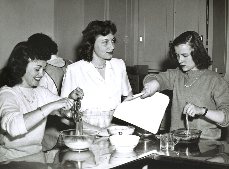 A photo of veteran wives participating in a cooking class. The woman pictured at the center is Evelyn Brumsted, wife of Harlan Brumsted '46.